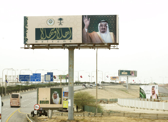 Billboards with photos of Saudi King Salman and Arabic that reads,