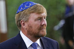 """King Willem-Alexander arrives to unveil a new monument in the heart of Amsterdam's historic Jewish Quarter on Sunday, Sept. 19, 2021, honoring the 102,000 Dutch victims of the Holocaust. Designed by Polish-Jewish architect Daniel Libeskind, the memorial is made up of walls shaped to form four Hebrew letters spelling out a word that translates as """"In Memory Of."""" The walls are built using bricks each of which is inscribed with the name of one of the 102,000 Jews, Roma and Sinti who were murdered in Nazi concentration camps during World War II or who died on their way to the camps. (AP Photo/Peter Dejong)"""