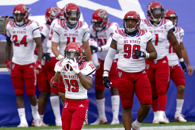 North Carolina State defensive back Josh Pierre-Louis (19) reacts with the team behind him as a penalty was called on him for roughing the passer on a play where safety Jakeen Harris (6) intercepted a pass by Pittsburgh Panthers quarterback Kenny Pickett (8) and ran it back for a touchdown in the first half of an NCAA college football game, Saturday, Oct. 3, 2020, in Pittsburgh. (AP Photo/Keith Srakocic)