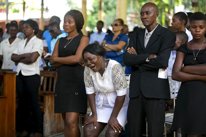 Relatives attend a funeral for people who were killed in the past weeks' protest, in Port-au-Prince, Haiti, Tuesday, Nov. 19, 2019. More than 40 people have been killed and dozens injured in more than two months of demonstrations organized by opposition leaders demanding the resignation of President Jovenel Moïse amid anger over corruption, ballooning inflation and a scarcity of basic goods. (AP Photo/Dieu Nalio Chery)