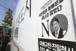 A poster with an image of Japanese Prime Minister Shinzo Abe denouncing Japan's trade restrictions is seen on a street in Seoul, South Korea, Tuesday, Nov. 5, 2019. South Korean President Moon Jae-in and Japanese Prime Minister Shinzo Abe met one-on-one Monday for the first time in more than a year and called for more dialogue between the countries to settle a deep dispute over trade and history. The sign reads