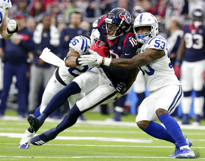 Houston Texans wide receiver DeAndre Hopkins (10) is hit by Indianapolis Colts strong safety Clayton Geathers (26) and linebacker Duke Ejiofor (53) after making a catch during the first half of an NFL wild card playoff football game, Saturday, Jan. 5, 2019, in Houston. (AP Photo/Michael Wyke)