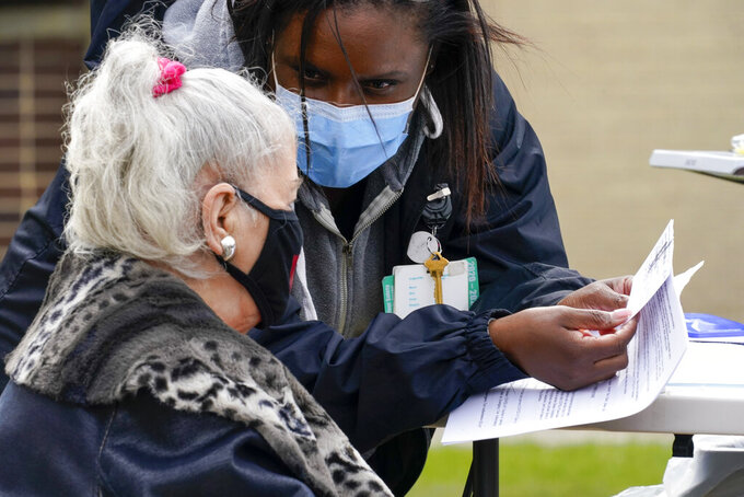 A nurse goes over the vaccination card with Sarah Luisi, of Uniondale, N.Y., before inoculating her with the Johnson & Johnson's one-dose COVID-19 vaccine at the Vaxmobile, at the Uniondale Hempstead Senior Center, Wednesday, March 31, 2021, in Uniondale, N.Y. The Vaxmobile, is a COVID-19 mobile vaccination unit, sponsored by a partnership between Mount Sinai South Nassau and Town of Hempstead to bring the one-dose vaccine directly to hard-hit communities in the area. (AP Photo/Mary Altaffer)
