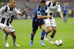 Inter Milan's Alexis Sanchez challenges for the ball with Udinese's Antonin Barak during a Serie A soccer match between Inter Milan and Udinese, at the San Siro stadium in Milan, Italy, Saturday, Sept. 14, 2019. (AP Photo/Luca Bruno)