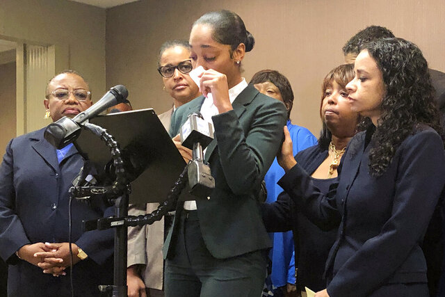 FILE - In this Sept. 25, 2019 file photo, Jazmyne Childs, center, cries during a news conference in Raleigh, N.C., as she describes the sexual harassment she says she endured while employed by the North Carolina chapter of the NAACP. Childs is suing the national NAACP group and her ex-supervisor, the Rev. Curtis Gatewood, according to a lawsuit filed Monday, Feb. 3, 2020. She is seeking at least $15 million for her emotional and mental distress that she says civil rights organization condoned through its inaction.  (AP Photo/Martha Waggoner, File)