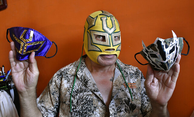 In this May 14, 2020, photo, local wrestler El Universitario holds some of his homemade face masks, in Laredo, Texas. One local luchador is using his fame in the ring and his skills as a tailor by trade to bring to life some pride for the Mexican Lucha during the COVID-19 pandemic. El Universitario - which he prefers to be identified as to protect his true identity from the public - is doing this by making customizable face masks of legendary Mexican wrestlers Blue Demon, El Santo and Mil Mascaras. (Cuate Santos/The Laredo Morning Times via AP)