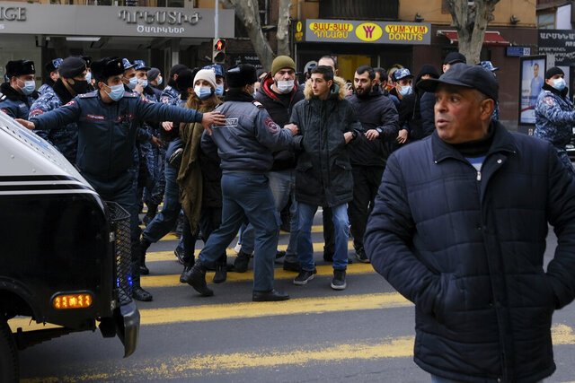 Police try to block demonstrators during a rally demanding the resignation of the country's prime minister over his handling of the conflict with Azerbaijan over Nagorno-Karabakh in Yerevan, Armenia, Tuesday, Dec. 8, 2020.Armenian opposition politicians and their supporters have been calling for Prime Minister Nikol Pashinyan to step down ever since he signed a peace deal that halted 44 days of deadly fighting over the separatist region, but called for territorial concessions to Azerbaijan. (Aram Kirakosyan/PAN Photo via AP)