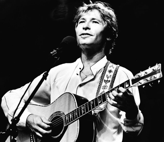 "FILE - In this July 28, 1983, file photo, singer John Denver strums his guitar as he performs during an outdoor concert on the Boston Common, in Boston, Mass. Denver's song, ""Country Roads,"