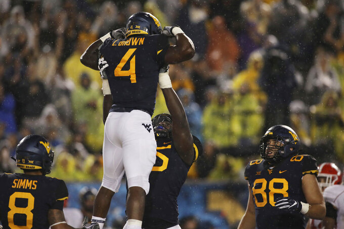 West Virginia running back Leddie Brown (4) is lifted by offensive lineman Yodny Cajuste (55) after scoring a touchdown during the second half of an NCAA college football game against Youngstown State on Saturday, Sept. 8, 2018, in Morgantown, W.Va. (AP Photo/Raymond Thompson)