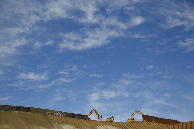 FILE- Workers replace sections of the border wall separating San Diego from Tijuana, Mexico, left, with new sections, right, Tuesday, Jan. 8, 2019, seen from Tijuana. Top Trump administration officials will visit South Texas five days before Election Day to announce they have completed 400 miles of U.S.-Mexico border wall, attempting to show progress on perhaps the president's best-known campaign promise four years ago. But most of the wall went up in areas that already had smaller barriers. (AP Photo/Gregory Bull)