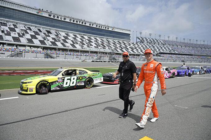 Driver Harrison Burton, right, walks to his vehicle on pit road before a NASCAR Xfinity Series auto race at Daytona International Speedway, Saturday, Aug. 28, 2021, in Daytona Beach, Fla. (AP Photo/Phelan M. Ebenhack)