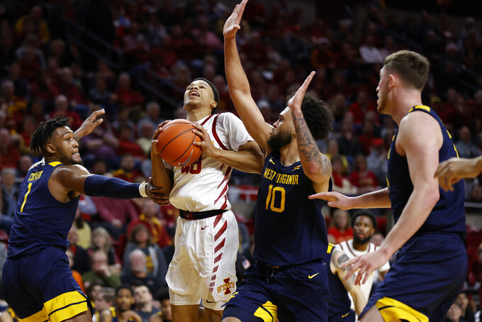 Iowa State guard Rasir Bolton, center, drives the ball inside as West Virginia forward Derek Culver, left, and guard Jermaine Haley, right, defend during the first half of an NCAA college basketball game Tuesday, March 3, 2020, in Ames, Iowa. (AP Photo/Matthew Putney)