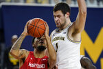 Maryland guard Eric Ayala, left, is defended by Michigan center Hunter Dickinson (1) during the first half of an NCAA college basketball game, Tuesday, Jan. 19, 2021, in Ann Arbor, Mich. (AP Photo/Carlos Osorio)