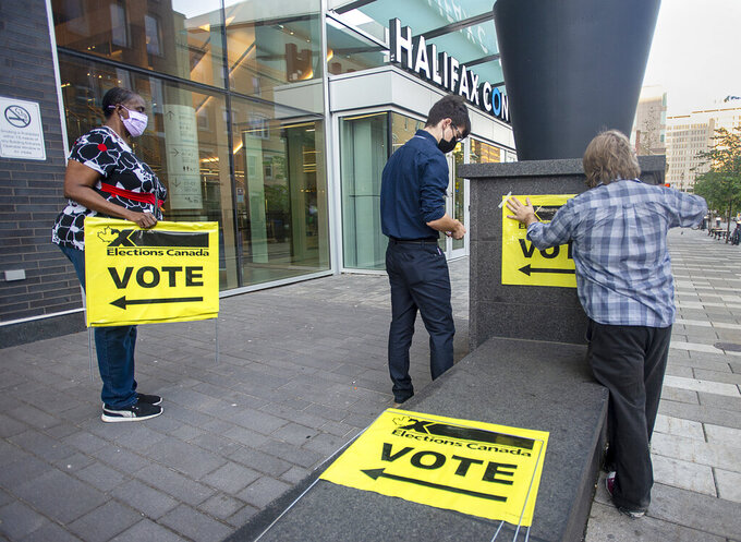Elections Canada workers place signage at the Halifax Convention Centre as they prepare for the polls to open in the federal election in Halifax on Monday, Sept. 20, 2021.  (Andrew Vaughan/The Canadian Press via AP)