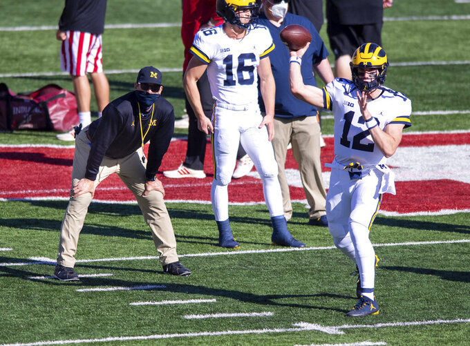 Michigan head coach Jim Harbaugh, left, watches as quarterback Cade McNamara (12) warms up before an NCAA college football game against Indiana, Saturday, Nov. 7, 2020, in Bloomington, Ind. (AP Photo/Doug McSchooler)