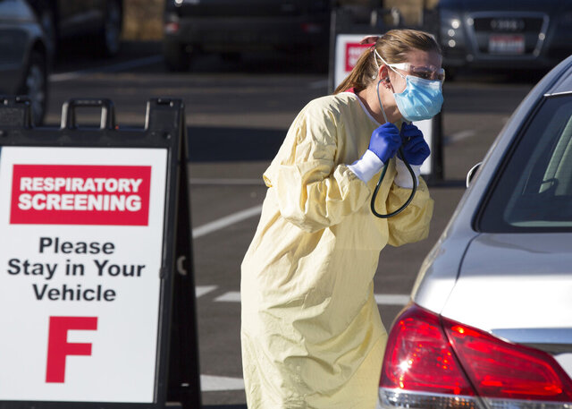 Physician assistant Nicole Thomas conducts a COVID-19 examination in the parking lot at Primary Health Medical Group's clinic in Boise, Idaho, Tuesday, Nov. 24, 2020. The urgent-care clinic revamped into a facility for coronavirus patients as infections and deaths surge in Idaho and nationwide. Some 1,000 people have died due to COVID-19, and infections this week surpassed 100,000. (AP Photo/Otto Kitsinger)