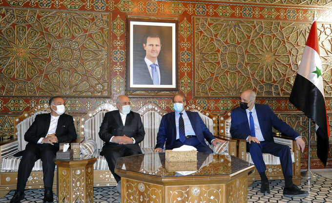 In this photo released by the Syrian official news agency SANA, Syria's Foreign Minister Faisal Mekdad, second right, receives his Iranian counterpart Mohammad Javad Zarif, second left, in Damascus, Syria, Wednesday, May 12, 2021. Zarif said his country is ready for closer ties with its regional rival Saudi Arabia, saying Wednesday he hoped recent talks would lead to greater stability in the region. A picture of Syrian President Bashar Assad hangs on the wall. (SANA via AP)