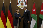 German Defense Minister Annegret Kramp-Karrenbauer, left, shakes hands with Jordan's Foreign Minister Ayman Safadi, in Amman, Jordan, Monday, Aug. 19, 2019. It was Kramp-Karrenbauer's first trip abroad as Defense Minister. (AP Photo/Raad Adayleh)