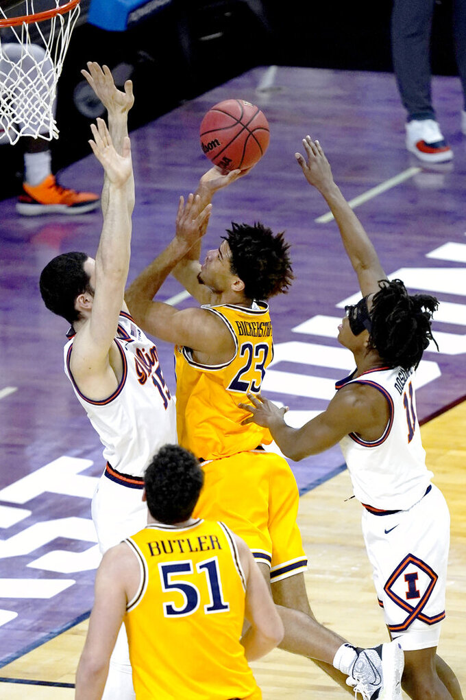 Drexel's T.J. Bickerstaff (23) shoots between Illinois forward Giorgi Bezhanishvili (15) and Ayo Dosunmu, during the first half of a first round NCAA college basketball tournament game Friday, March 19, 2021, at the Indiana Farmers Coliseum in Indianapolis .(AP Photo/Charles Rex Arbogast)