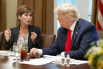 FILE - In this June 13, 2019, file photo, Iowa Gov. Kim Reynolds talks with President Donald Trump during a meeting with governors on