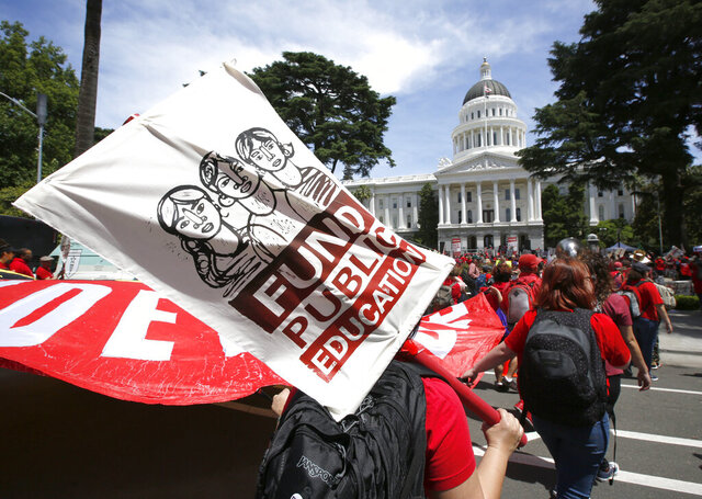FILE — In this May 22, 2019 file photo members of the California Teachers Association and proponents of public education march to the Capitol in Sacramento, Calif., calling for an increase in funding for public schools. Supporters of a proposed amendment to the California Constitution that would raise property taxes on some businesses say they have collected more than 1.7 million signatures. The Schools & Communities First campaign announced Thursday, April 2, 2020 it has submitted the signatures to state officials. (AP Photo/Rich Pedroncelli, File)