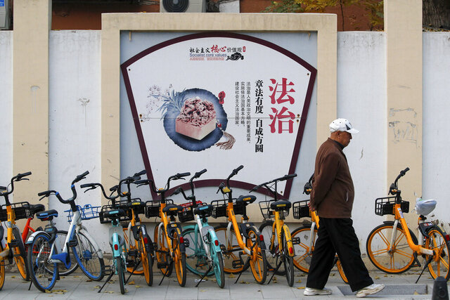 A man walks by a propaganda board depicting China's legal system promoting the government's socialist core values near residential buildings in Beijing, Wednesday, Nov. 11, 2020. A prominent Chinese pig farmer who has publicly praised the work of lawyers who help the public amid a crackdown on legal activists by President Xi Jinping's government was subjected Monday to unspecified