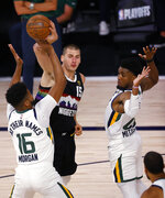 Denver Nuggets' Nikola Jokic tries to pass the ball as Utah Jazz's Juwan Morgan, left, defends during the second quarter of Game 5 of an NBA basketball first-round playoff series, Tuesday, Aug. 25, 2020, in Lake Buena Vista, Fla. (Mike Ehrmann/Pool Photo via AP)