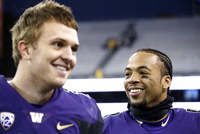 Washington quarterback Jake Browning, left, and tailback Myles Gaskin smile after being interviewed following an NCAA college football game against Oregon State, Saturday, Nov. 17, 2018, in Seattle. (AP Photo/Elaine Thompson)