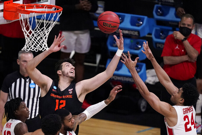 Oregon State center Roman Silva (12) fights for a rebound with Houston guard Quentin Grimes (24) during the first half of an Elite 8 game in the NCAA men's college basketball tournament at Lucas Oil Stadium, Monday, March 29, 2021, in Indianapolis. (AP Photo/Michael Conroy)