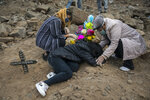Aurora Davila, right, comforts her grieving 15-year-old granddaughter Tatiana Palomo as she lies on the grave of her father who died from the new coronavirus, during a burial service at the