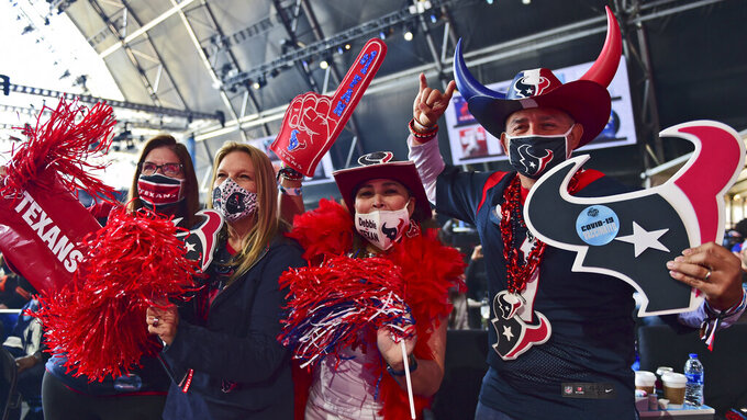 Houston Texans fans celebrate after the Texans selected Brevin Jordan, a tight end from the University of Miami, in the fifth round of the NFL football draft, Saturday, May 1, 2021, in Cleveland. (AP Photo/David Dermer)