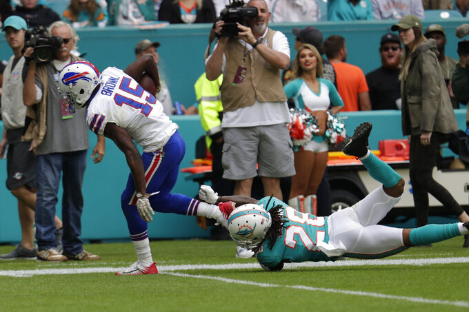 Buffalo Bills wide receiver John Brown (15) escapes a take by Miami Dolphins strong safety Bobby McCain (28) to score a touchdown, during the first half at an NFL football game, Sunday, Nov. 17, 2019, in Miami Gardens, Fla. (AP Photo/Lynne Sladky)