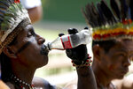 A representative of the Huitoto and Ticuna indigenous communities drinks a soda, outside the room where leaders of several South American nations that share the Amazon are meeting, in Leticia, on Colombia's Amazon river border with Brazil and Peru, Friday, Sept. 6, 2019. Presidents and representatives from several countries in South America's Amazon region met to discuss a joint strategy for preserving the world's largest rain forest, which has been under threat from a record number of wildfires.(AP Photo/Fernando Vergara)