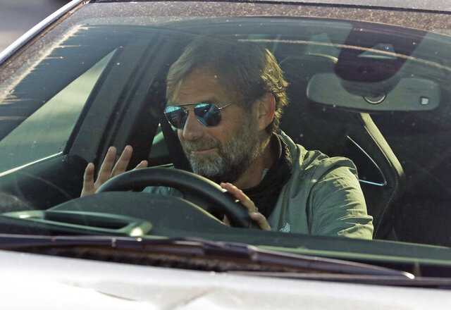 Liverpool soccer team manager Jurgen Klopp waves as he arrives at the club's Melwood training ground after the English Premier League announced players can return to training in small groups as the coronavirus lockdown is eased Wednesday May 20, 2020. (Peter Byrne/PA via AP)