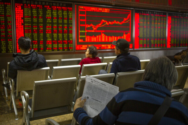 A Chinese investor reads a newspaper as she monitors stock prices at a brokerage house in Beijing, Friday, Jan. 10, 2020. Asian shares rose Friday as worries receded the United States and Iran might be stepping closer to the edge of war, and U.S. indexes hit records. (AP Photo/Mark Schiefelbein)