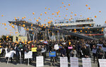 FILE - In this March 16, 2016, file photo, Officials of South Korean firms with plants in the now-suspended inter-Korean factory complex in North Korea's border town of Kaesong, release balloons during a rally at the Imjingak pavilion near the border village of Panmunjom in Paju, South Korea. The letters at banners read