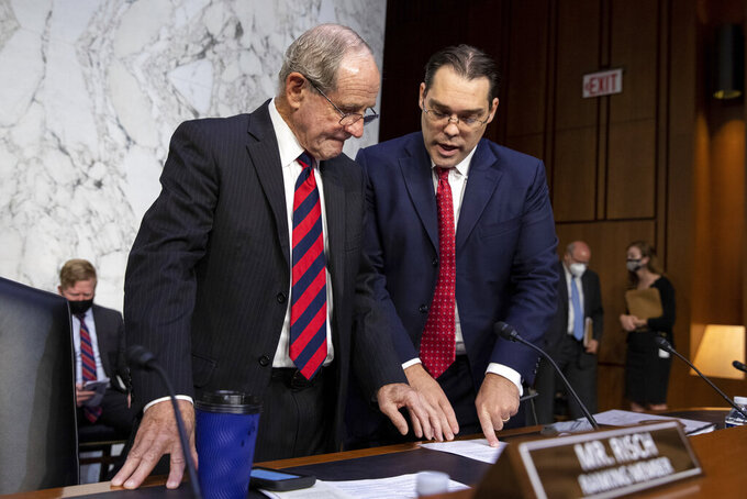 Sen. Jim Risch, R-Idaho, left, speaks to a staff member before a Senate Foreign Relations Committee meeting on Capitol Hill in Washington, Wednesday, Aug. 4, 2021. (AP Photo/Amanda Andrade-Rhoades)
