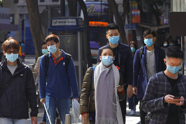 People wearing face masks walk on a downtown street in Hong Kong Friday, Feb. 21, 2020. COVID-19 viral illness has sickened tens of thousands of people in China since December. (AP Photo/Vincent Yu)