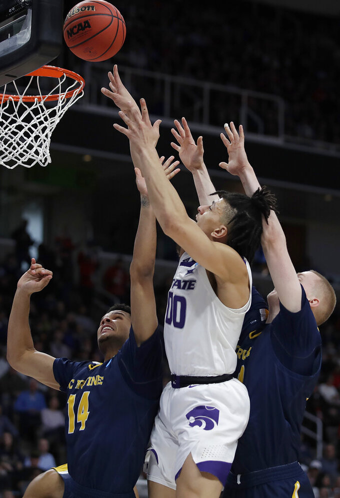 Kansas State guard Mike McGuirl, center, shoots against UC Irvine guard Evan Leonard, left, and UC Irvine forward Collin Welp during the second half of a first round men's college basketball game in the NCAA Tournament Friday, March 22, 2019, in San Jose, Calif. (AP Photo/Ben Margot)