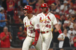 St. Louis Cardinals' Nolan Arenado, left, reacts after hitting a two-run home run during the eighth inning of a baseball game against the Cincinnati Reds on Saturday, Sept. 11, 2021, in St. Louis. (AP Photo/Joe Puetz)