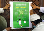 Workers place a poster with Arabic reads,