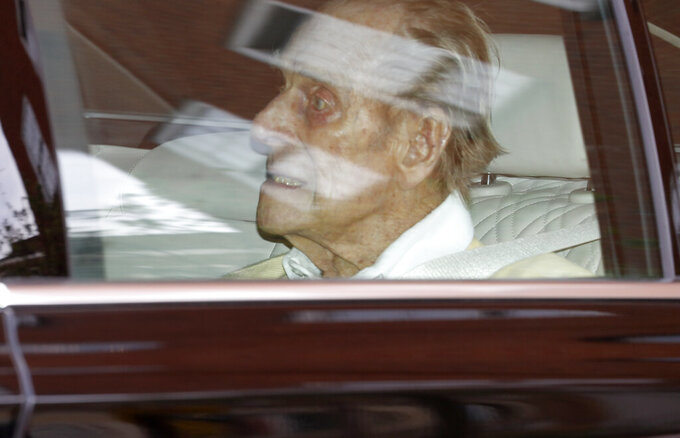Britain's Prince Philip leaves the King Edward VII hospital in the back of a car in London, Tuesday, March 16, 2021. The 99-year-old husband of Queen Elizabeth II has been hospitalized after a heart procedure. (AP Photo/Alastair Grant)