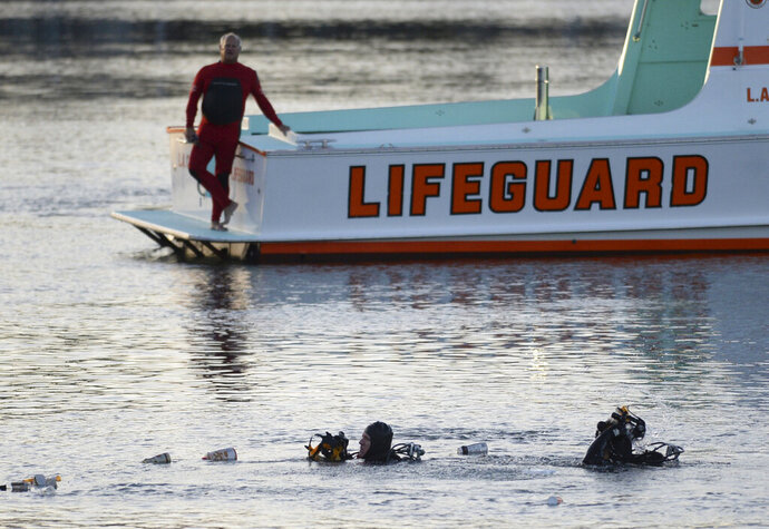 FILE - In this April 9, 2015 file photo, divers emerge from the water as debris believed to be from a car floats to the surface where a car went off a pier and into the water in Los Angeles' San Pedro harbor district. Los Angeles prosecutors have charged an Egyptian father with murder after he allegedly drove his family off a pier, killing his two autistic sons. The district attorney's office said Wednesday, July 17, 2019 there's a special circumstance allegation that the killings were carried out by Ali Elmezayen for financial gain.  (Steve McCrank/The Orange County Register via AP, File)