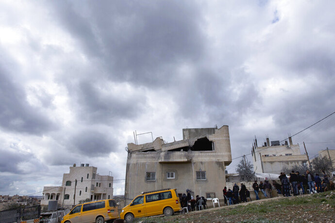 Palestinians gather by Khalil Jabarin's demolished apartment in the family house, in the West Bank village of Yatta, south of Hebron, Friday Jan. 18, 2019. Jabarin is charged with stabbing to death an Israeli in a West Bank settlement. (AP Photo/Nasser Nasser)