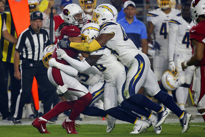 Arizona Cardinals wide receiver Larry Fitzgerald, left is tackled by Los Angeles Chargers defensive back Desmond King (20), Los Angeles Chargers defensive back Desmond King, rear, and Los Angeles Chargers outside linebacker Kyzir White, right, during the first half of an NFL preseason football game, Thursday, Aug. 8, 2019, in Glendale, Ariz. (AP Photo/Ross D. Franklin)