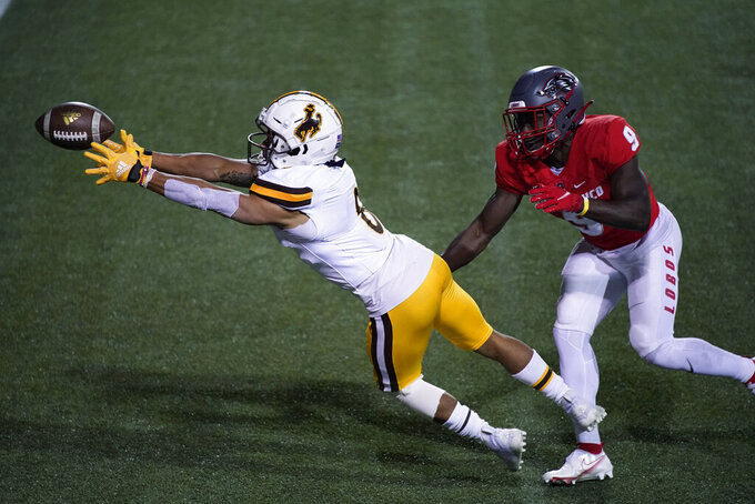 Wyoming wide receiver Dontae Crow (8) misses a catch next to New Mexico safety Jerrick Reed II (9) during the first half of an NCAA college football game Saturday, Dec. 5, 2020, in Las Vegas. (AP Photo/John Locher)