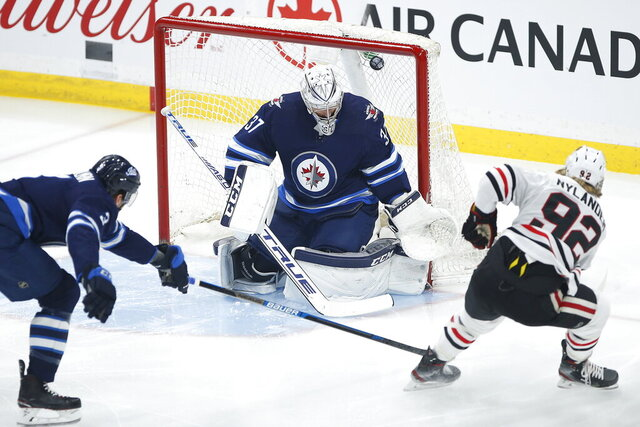 Winnipeg Jets goaltender Connor Hellebuyck (37) fails to stop a shot from Chicago Blackhawks' Alex Nylander (92) as Jets' Tucker Poolman (3) also defends during first-period NHL hockey game action in Winnipeg, Manitoba, Thursday, Dec. 19, 2019. (John Woods/The Canadian Press via AP)