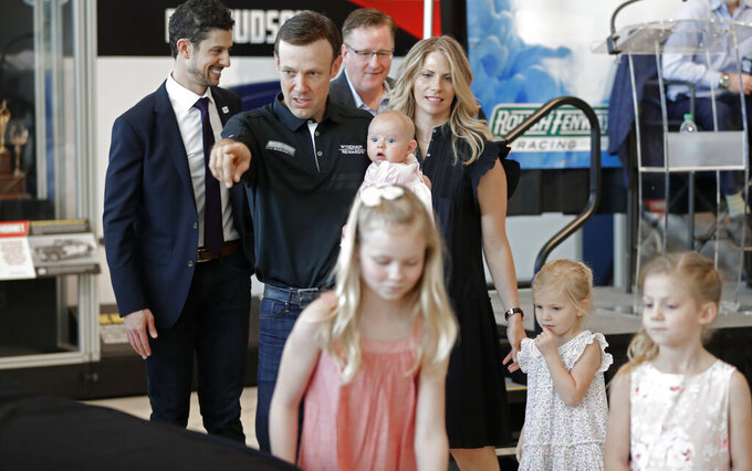 FILE - In this April 25, 2018, file photo, NASCAR driver Matt Kenseth gestures towards a race car as he walks with his family before unveiling the car during a news conference in Charlotte, N.C. Kenseth had the best summer of his life last year, when he traveled with his wife and four daughters, made his first visit to Europe and took up marathon running. It was a blissful retirement, yet he gave it up this week when he agreed to return to NASCAR as the replacement for fired driver Kyle Larson. At 48, he will be the oldest driver in the field when racing resumes. (AP Photo/Chuck Burton, File)
