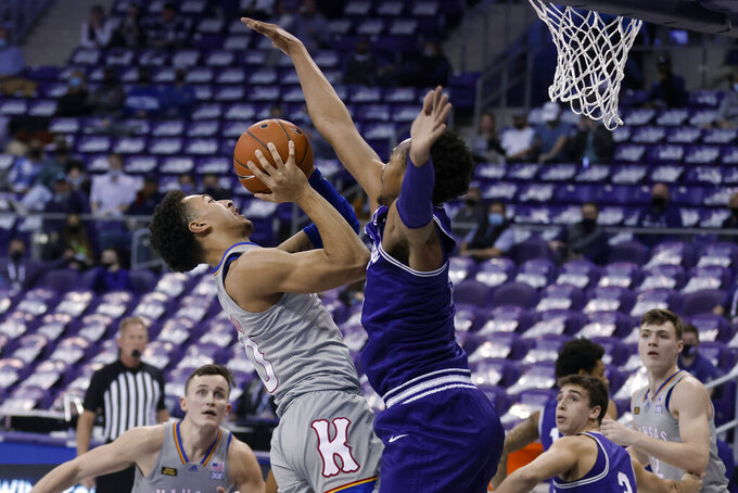 Kansas forward Jalen Wilson (10) falls back before taking a shot as TCU forward Chuck O'Bannon Jr., center right, defends during the first half of an NCAA college basketball game in Fort Worth, Texas, Tuesday, Jan. 5, 2021. (AP Photo/Ron Jenkins)