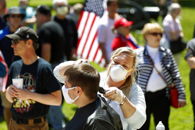 Brandi Bates gives Mike Greenbauer a free haircut at the State Capitol during a rally in Lansing, Mich., Wednesday, May 20, 2020. Barbers and hair stylists are protesting the state???s stay-at-home orders, a defiant demonstration that reflects how salons have become a symbol for small businesses that are eager to reopen two months after the COVID-19 pandemic began. (AP Photo/Paul Sancya)